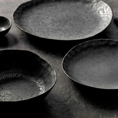 Beautiful product shot of the Rania collection of ceramic dinner plates and bowls on a dark tabletop