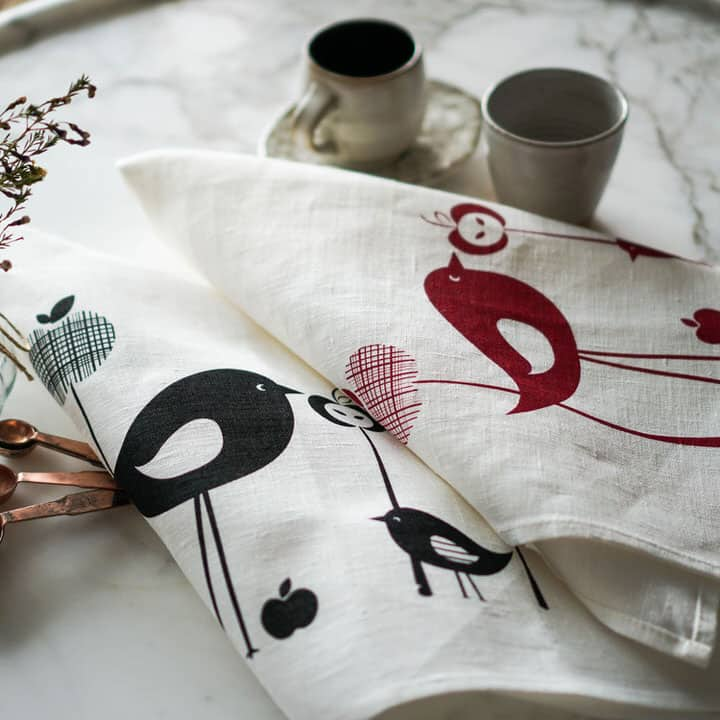 Styled product shot of Vinyl Design birds and apples red and black linen tea towels