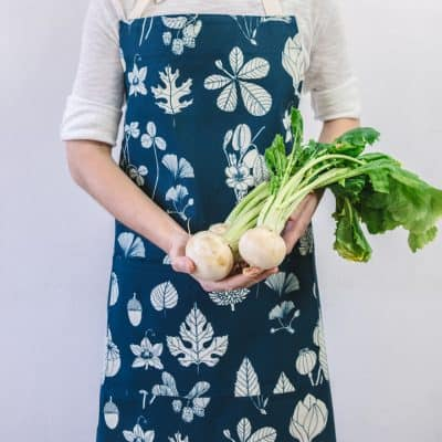 Modelled shot of Softer+Wild botanical print cotton apron in indigo