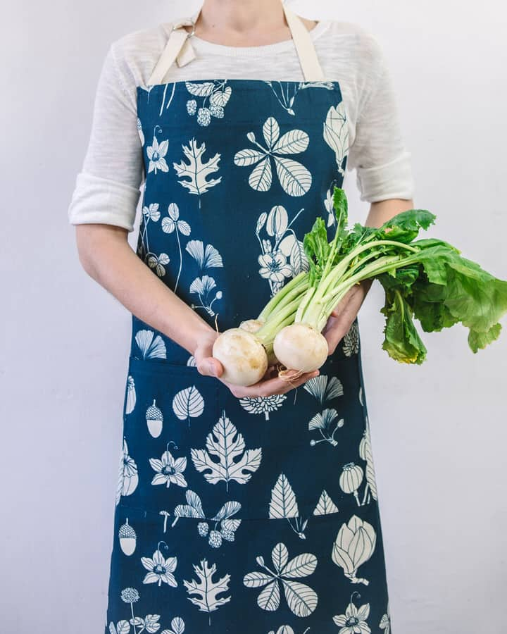 Modelled shot of Softer+Wild botanical print cotton apron in indigo