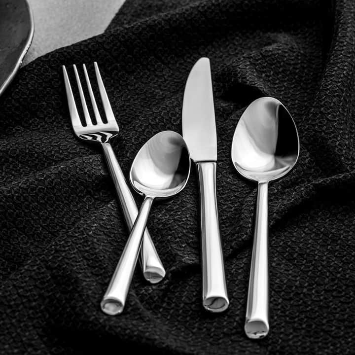 Lifestyle product shot of Shervin Verkil Beauty Range of cutlery set on a black cloth on a tabletop