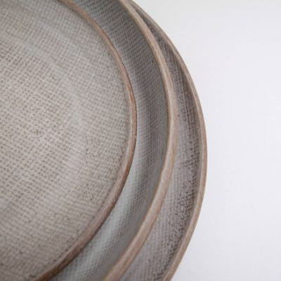 Sofia Ceramics Lifestyle shot of a stack of 3 Linen Collection Ivory dinner plate