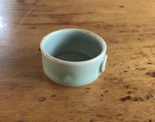 Product shot of Sally Gordon Wave handmade ceramic ramekin on wooden table