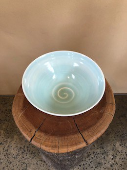 Lifestyle shot of ceramic Wobbly Bowl on wooden plate
