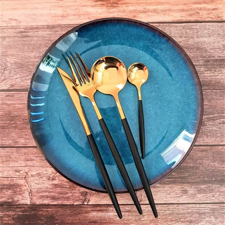 table setting with blue plate and golden black cutlery set