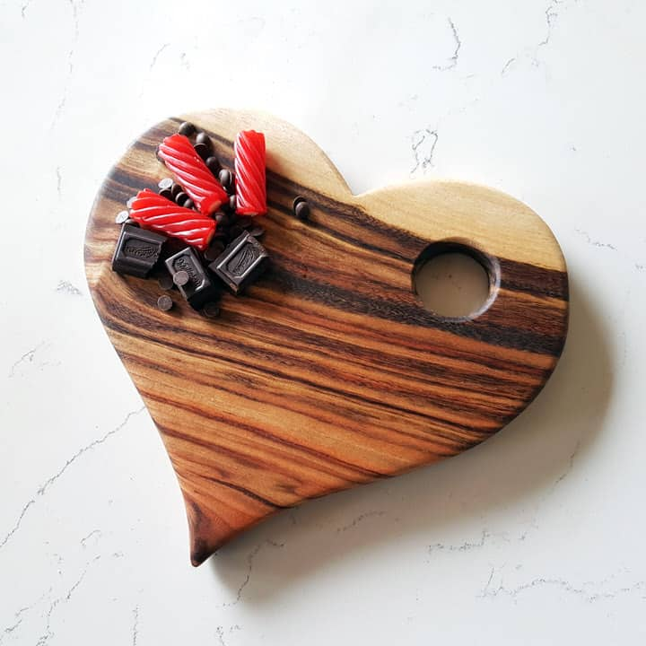 Blank heart shaped wooden serving board with chocolates and lollies