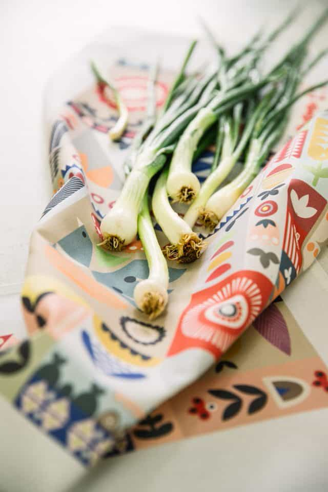 Garden tea towel with bunch of spring onions closeup